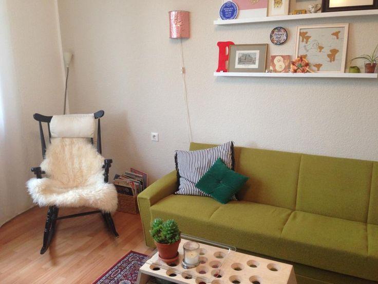 Grünes Sofa, gemütlicher Schaukelstuhl und kreative Regaldeko ...