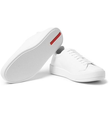 Each pair of Prada shoes is hand-assembled in Italy from as many as 85 pieces of leather. These minimal white sneakers have a clean-lined appearance and are detailed solely with a silver designer tab on the tongues, and red inserts on the base. The padded collars and rubber soles ensure a comfortable stride.
