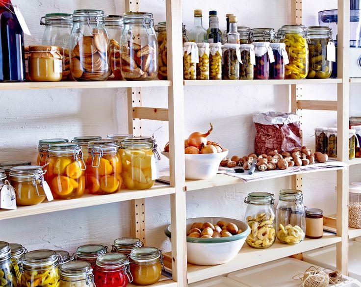 Tre scaffali in legno con contenitori per alimenti e bottiglie.