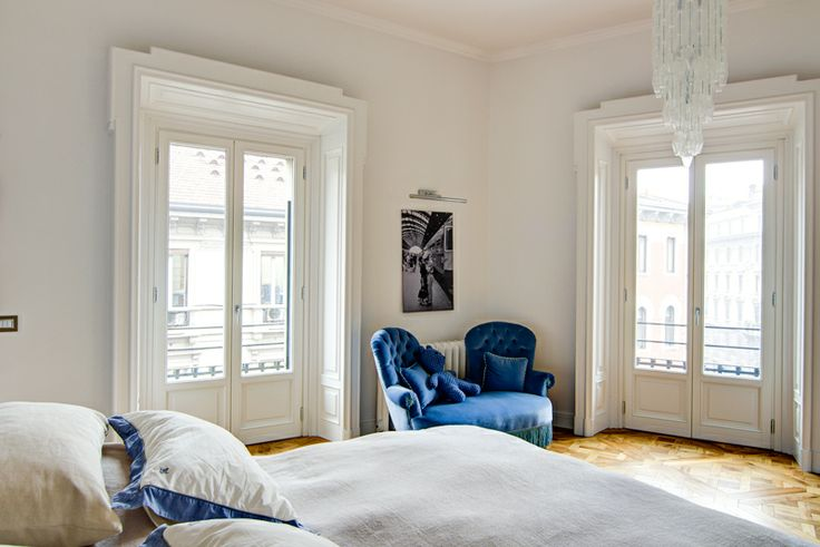A classy chic apartment in central Milan by Nomade Architettura http://www.nomadearchitettura.com/#all  bedroom, custom made bed, linen, blue sofa velvet, murano chandeliers, view to bathroom, white frames over doors and windows