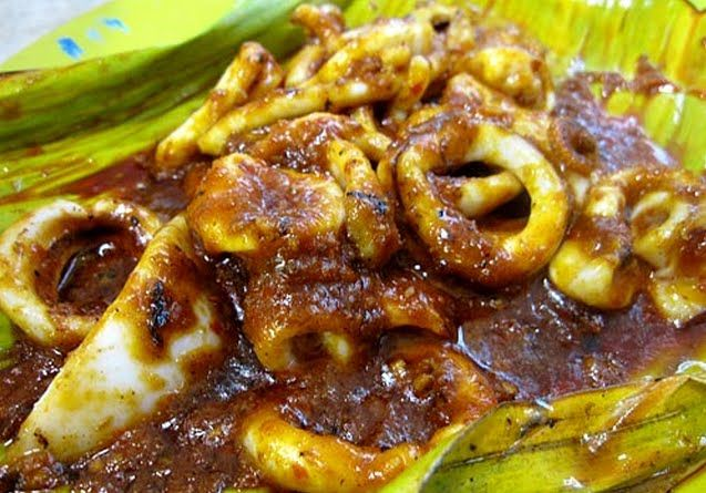 Sambal Sotong (Spicy Squid) - 1 lb fresh squid, cleaned, head discarded, sliced into thin rings. 4 Tbsp peanut or vegetable oil, 1 large onion,  2 ripe tomatoes, 1 Tbsp tamarind paste, 1 cup water, 1-2 tsp palm sugar or dark brown sugar, salt, 8-10 shallots, 2 tsp belacan, 4 cloves garlic, 5 tbsp chili paste, 4 candlenuts (buah keras/kemiri nuts)