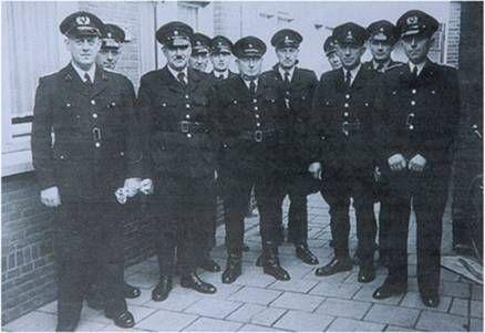 De politie kleding van de jaren 50. Het waren hoge hoeden en zwarte kleding. De mannen hadden vaak een snor.