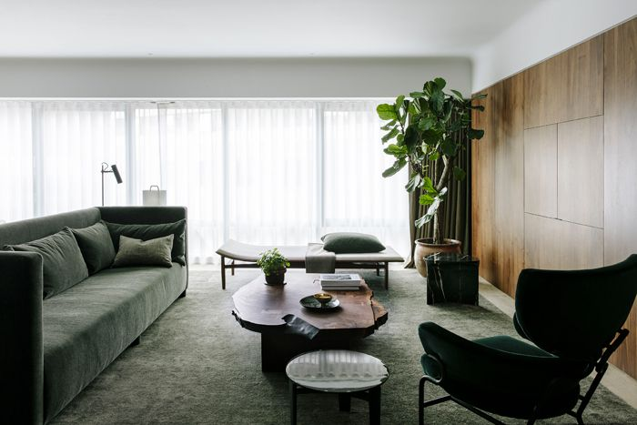 Un grand canapé dessine le côté salon, et fait face à la longue cloison en noyer d'Amérique qui permet de cacher écran de télévision, câbles et toutes les installations technologiques d'un appartement ultraconnecté.