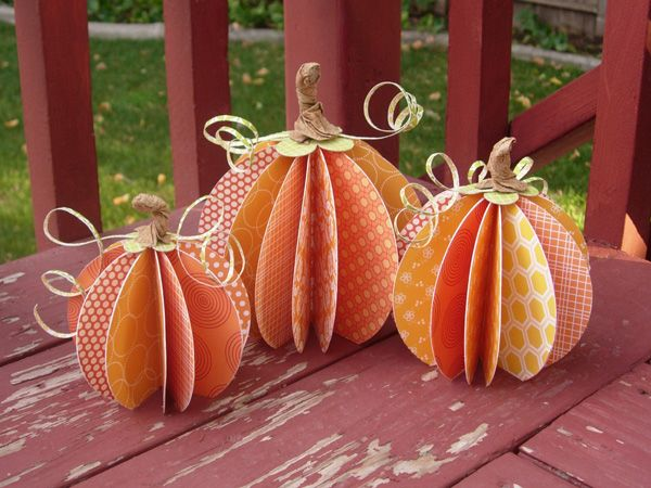 <3 THIS  cut 12 circles each: 4 inches, 5 inches, and 6 inches.   folded them, orange sides together, and then adhered the opposite sides together until have a 3D sphere. cut a bit off the bottom, so they'd stand straight.  add a green canvas flower, some rolled strips of green paper, and  make the stems by spraying a 2 inch strip of kraft soup staples with water, and then scrunching and twisting into a stem shape.