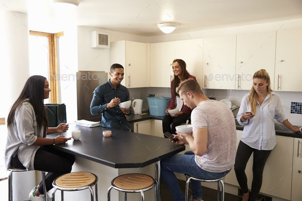 Students Relaxing In Kitchen Of Shared Accommodation by monkeybusiness. Students Relaxing In Kitchen Of Shared Accommodation