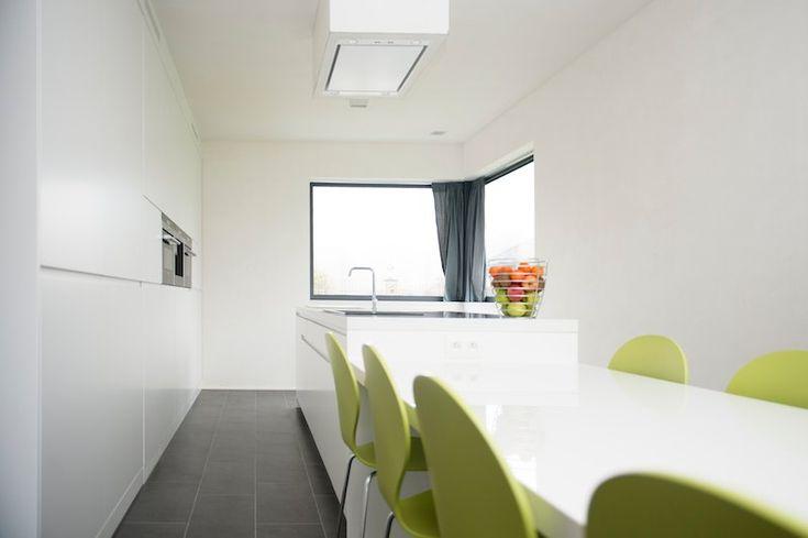 Strakke witte keuken met maatkasten en groene stoelen | www.biwood.be