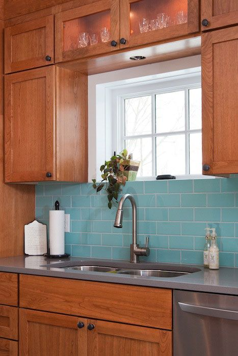 Pairing wood cabinets with a bold and bright backsplash, really brings the cabinets into the current century, and makes them feel all shiny and new.