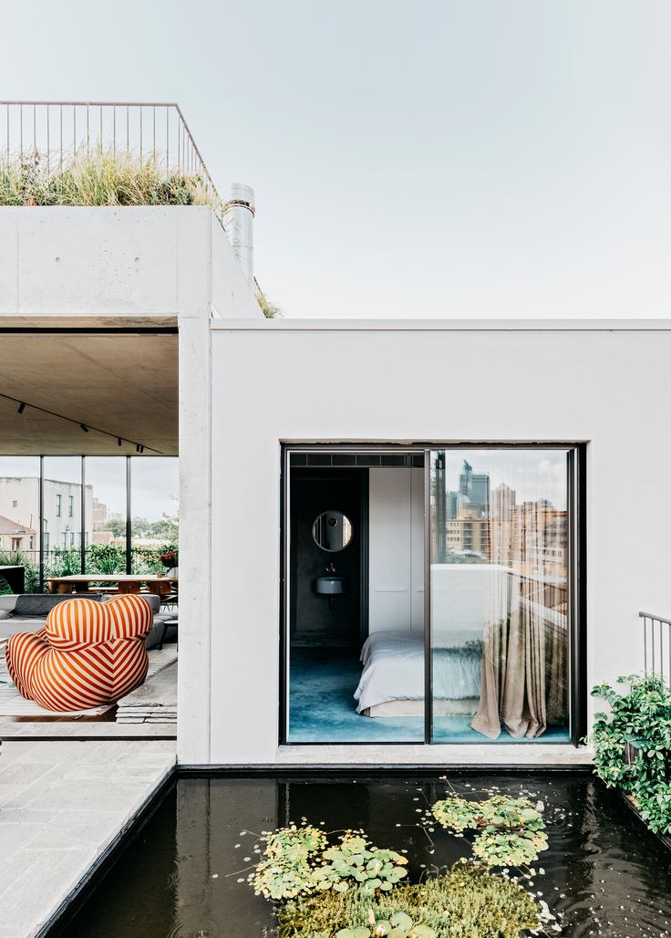 The guest bedroom in this sky-high Sydney apartment overlooks a fish pond.