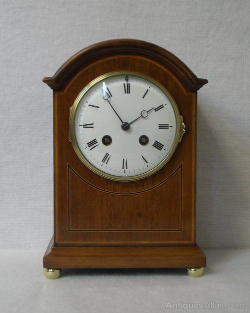 A good quality Edwardian arch top mahogany and boxwood string inlay Mantel Clock. The Clock has a white enamel dial with an eight day French movement which strikes the hours and half hours on a gong.
