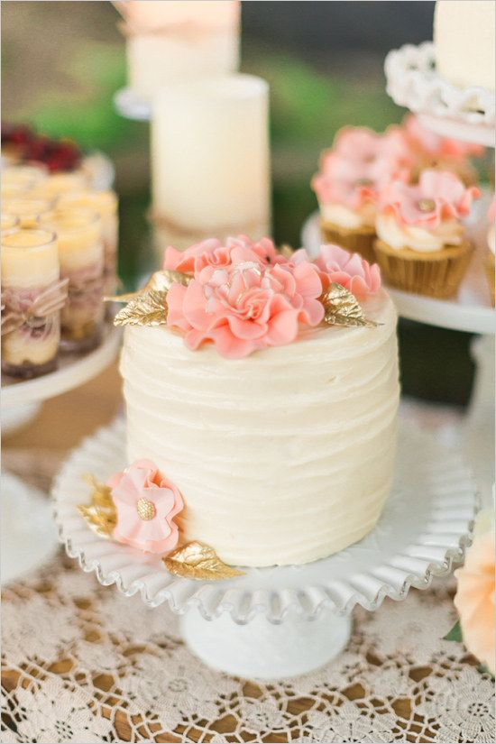 A buttercream cake with fun pink flowers and gold leaves.
