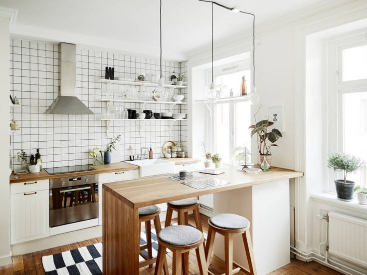 Black and white tiles, light wooden surfaces and grey accents. Kitchen in Goteburg.