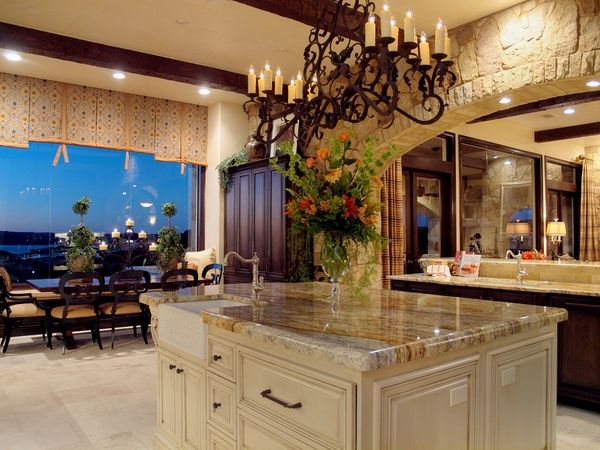 mediterranean kitchen yellow river granite countertops white kitchen island large wrough iron chandelier