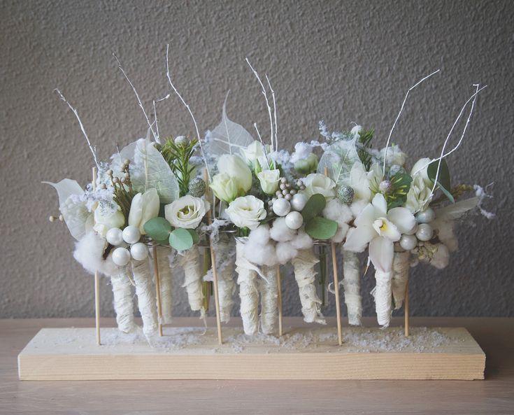 Winters bloemstuk. Gemaakt met besneeuwde asparagus en buisjes (omwikkeld met moerbeischors) gevuld met oa lisianthus, katoen, tulpen en cymbidium. #bloemstuk #kerst kerstmis #bloemen #tafelstuk #bloemschikken #bloemstyling #winter #snowwhite #flowers #christmas