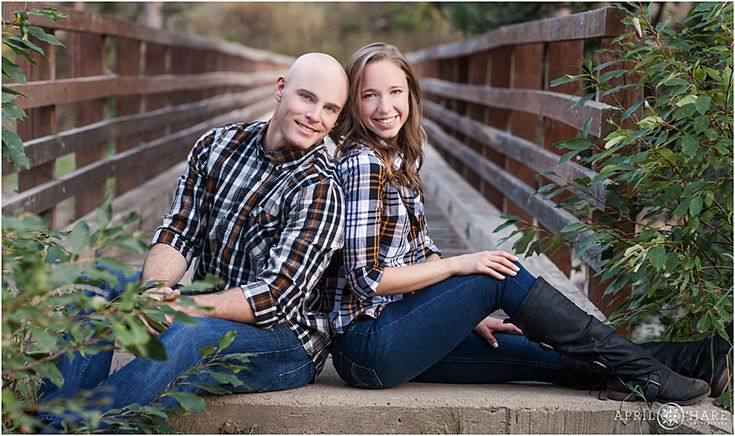 Engagement photos wearing plaid button up shirts on the bridge at Grey Rock Trailhead along the Poudre River near Fort Collins, Colorado. - April O'Hare Photography http://www.apriloharephotography.com #FortCollinsEngagement #FortCollinsPhotographer #ColoradoEngagement #ColoradoPhotographer #PoudreCanyon #GreyRockTrailhead