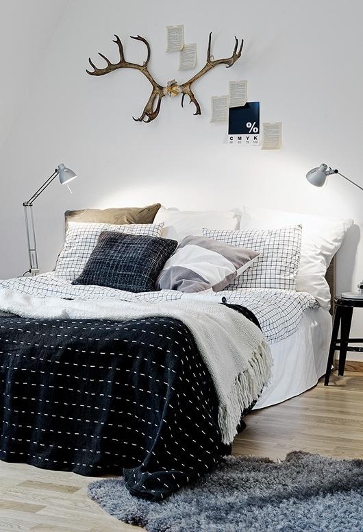Simpele slaapkamer waar verschillende materialen en printjes met elkaar worden afgewisseld. Leuk!