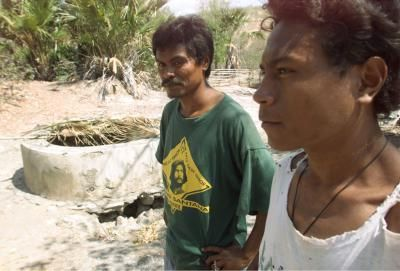 """BORBARA, EAST TIMOR - East Timorese men stand next to a well after finding the bones of at least four people inside it near the village of Borbara October 14, the likely victims of attacks by pro-Jakarta milita following a vote for independence from Indonesia. Dozens of bodies are suspected to be dumped in the area as witnesses said up to 100 locals were brought to the scene by militias in the days after the August 30 referendum for independence. Photo by Jason Reed (Reuters)."""""""