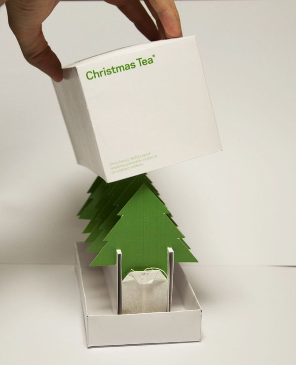 Christmas Tea by Maja Matas. Very clever packaging design. Trees come apart in halves along perforated line down middle. Tea bag attached to each half, & each half is designed to slip over cup edge. Designer says design is intended to encourage getting together at Christmas time with a dear person to share a hot beverage.