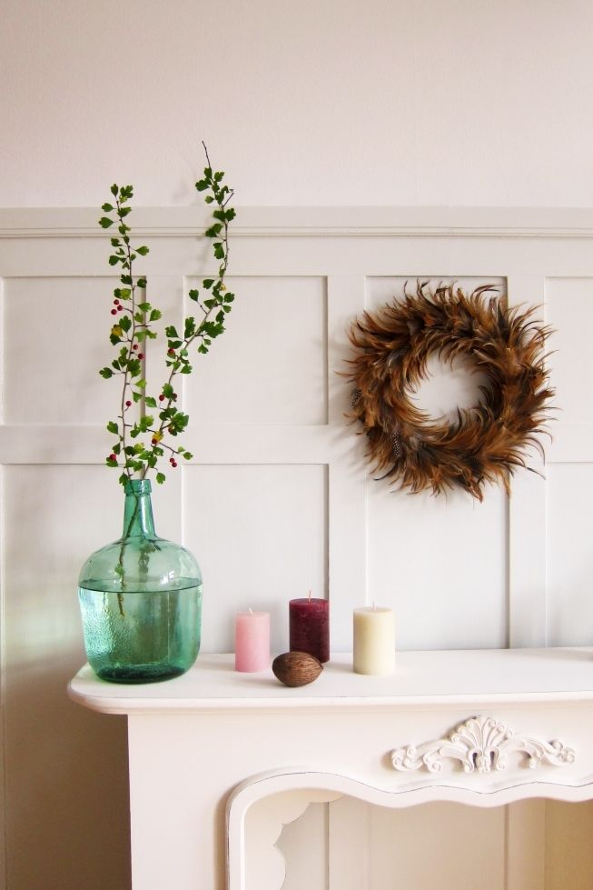 autumn fire place decoration - berry branches, warm colors, feathers, fall