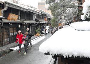 市街地で初めての積雪の中、古い街並みを歩く観光客、高山市上三之町で。Shigaichi de hajimete no sekisetsu no naka, furui machinami wo aruku kankoukyaku, Takayama-shi Kamisanno-machi de. Di dalam timbunan salju yang pertama di area kota, wisatawan yang berjalan di deretan rumah-rumah tua, di kota Kamisannno, Takayama.
