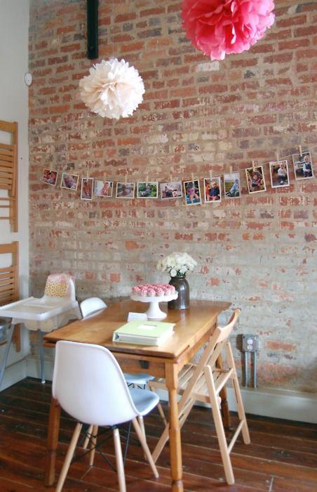 La ghirlanda di foto, la parete in mattoni, la sedia di Eames...