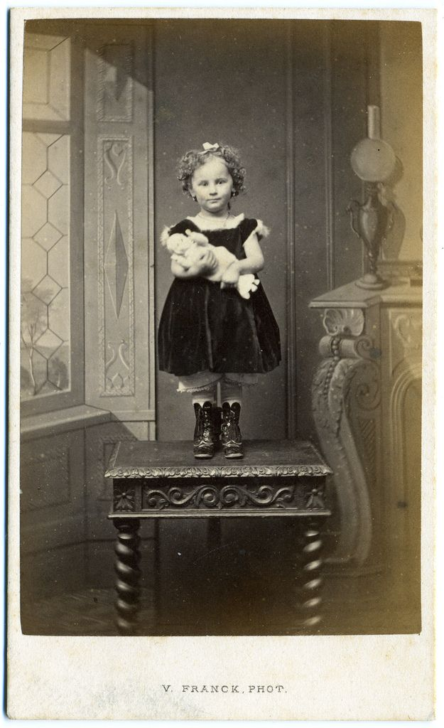 Claimed to be a post mortem - why? Lovely healthy little girl! Her arms look like they're moving, she's smiling, and the stand is there to stop her falling off the table. Beautiful picture!