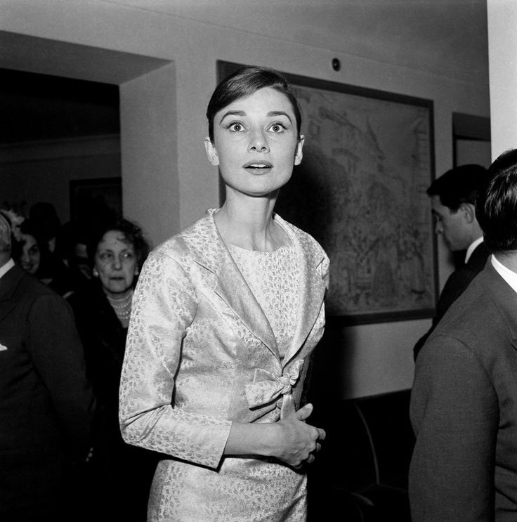 The actress Audrey Hepburn photographed by Elio Sorci at the famous Hotel Hassler, on Piazza Trinità dei Monti, in Rome (Italy), during a cocktail, on March 20, 1958.  Audrey was wearing:Cocktail ensemble: Givenchy (of brocade satin in a shade of light magenta, a cropped blazer, closed by the detail of a ribbon in the same tissue, sleeves with a height above the wrists, and a sleeveless dress with length below the knees, both pieces lined with silk crepe, of his haute couture collection for…
