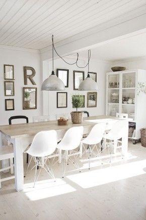 Grote eettafel met moderne witte stoelen en stoere lampen erboven. Mooie spiegels op de wand erachter.