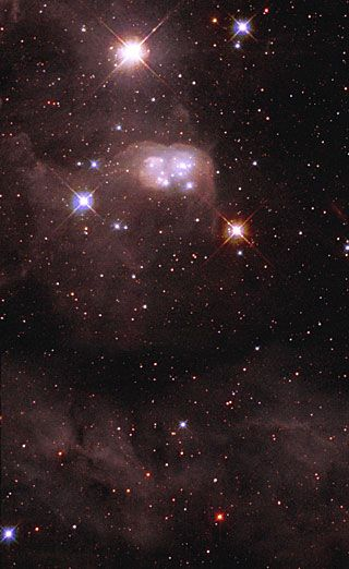 A unique peanut-shaped cocoon of dust, called a reflection nebula, surrounds a cluster of young, hot stars in this view from Hubble … the 'double bubble' called N30B is inside a larger nebula named DEM L 106...