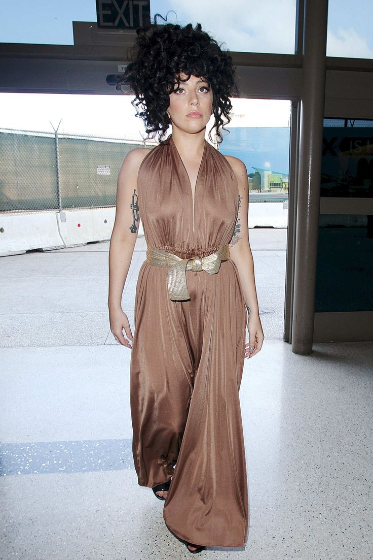 Yesterday, Lady Gaga broke her recent steak of wearing nothing but a T-shirt and fishnets and opted to travel in a long, flowing halter jumpsuit. She was spotted at LAX wearing her dark, curly wig of the moment along with billowing brown pant legs and a gold belt tied at her waist — unquestionably one of her more reasonable airport ensembles.
