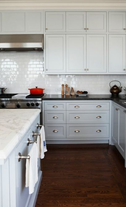 Kitchen cabinets were painted with Benjamin's Moore's Gentle Gray (with the color lightened, by 50 percent, on the upper cabinets). Narrow oak planks throughout the house match the original flooring.