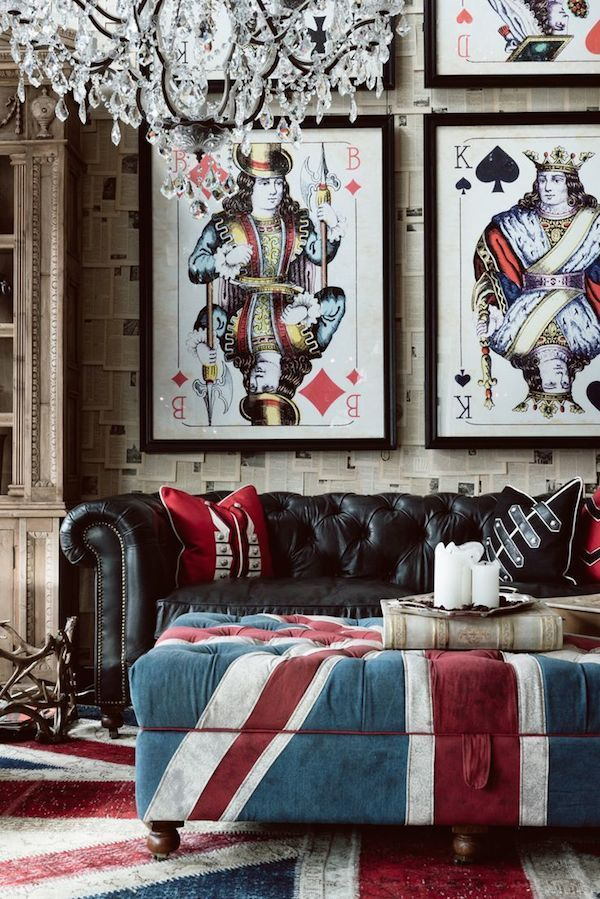 Such a whimsical living room with Union Jack ottoman, leather tufted sofa and deck of cards artwork.