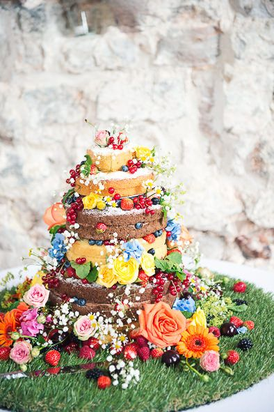 Naked Cake displayed on astro turf and decorated with fruits & flowers - Image by One Thousand Words - Vintage YSL Skirt For A Colourful 20s Inspired Wedding At The Lulworth Estate Dorset With Groom In Moss Bros. Suit And Images By One Thousand Words Wedding Photographers