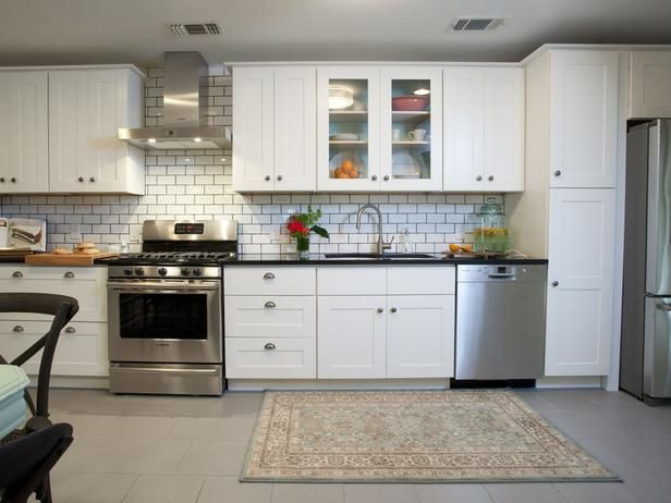this contemporary kitchen is light and modern with all new stainless steel appliances black countertops and grey tile flooring a white subway tile - Subway Kitchen Tiles Backsplash