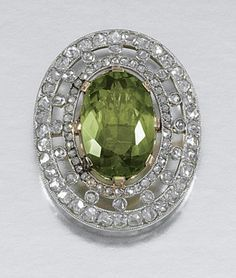 PERIDOT STICK PIN, EARLY 20TH CENTURY. Set to the centre with an oval peridot, within an open work frame millegrain-set with rose-cut diamonds, French assay and maker's marks.