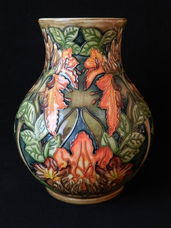 A modern Moorcroft vase tube line decorated with flowers and leaves