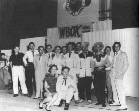 "September 1, 1955 - New Orleans at Ponchartrain Beach. - L- R: Scotty Moore, Jack Cardwell, Roy Parker, Jimmy Swan, Ernie Chaffin, Mrs. Jimmie Rogers, Al Terry, Jim Reeves, Jeff Bidderson, Lawton Williams, Luke McDaniel, Joe Clay, Elvis Presley with Ann Raye and ""Red"" Smith in front Photo courtesy Gene Leingang Jr."