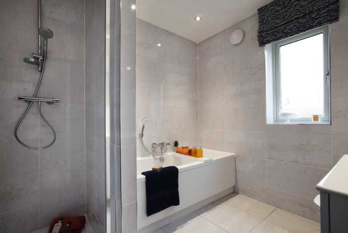The family bathroom is complete with a contemporary style white Roca bathroom suite with superb Porcelanosa tiling.