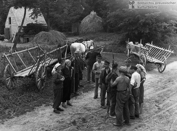 Members of the Worin Agricultural Cooperative in Oderbruch Discuss their Work (1955)  I found this picture interesting because women and men both worked in agriculture at the time in order to make money.