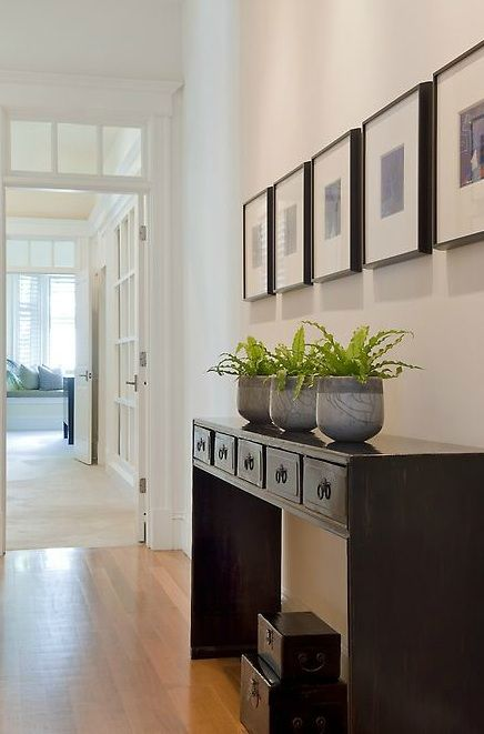 LOVE love love love love for our entryway! Simple zen-like foyer with glossy black console table, glossy black trunks, black & white photos in black gallery frames and trio of potted plants.