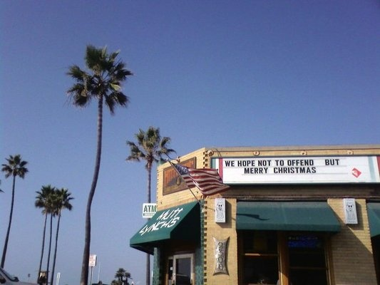 Mutt Lynch's, we hope not to offend but merry christmas, signs, palm trees, pub