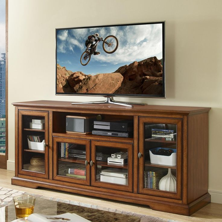 featuring adjustable shelves behind paned glass doors our sleek extra long tv stand offers a. Black Bedroom Furniture Sets. Home Design Ideas