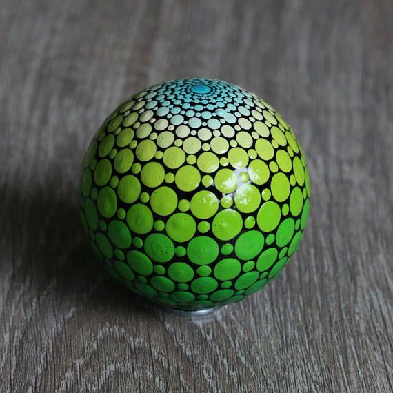 Mandala bal beschilderd met diverse groene kleuren acrylverf. De diameter van de bal is ongeveer 6 cm. De bal is gemaakt van zwart glas en afgewerkt met glanzende vernis. Maar kan alsnog niet gebruikt worden voor buiten, etc. Op de vierde foto is als voorbeeld te zien hoe de mandala bal verpakt is in een organza zakje met een metalen ringetje (waar de bal opgeplaatst kan worden). Leuk om dus kado te geven! Bijvoorbeeld voor een huwelijk, housewarming, geboorte of yoga leraar. Of gewoon leuk…
