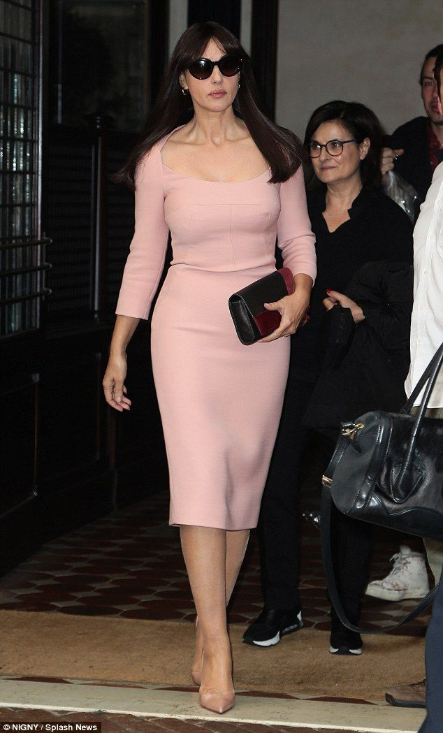 Breast foot forward: The Bond Girl drew attention to her ample bust in the skin-tight pastel midi dress which she colour co-ordinated with a pair of nude patent leather court heels