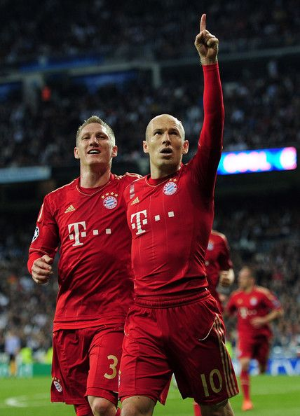 Arjen Robben of Bayern Munich celebrates scoring from the penalty spot with Bastian Schweinsteiger during the UEFA Champions League Semi Final second leg between Real Madrid CF and Bayern Munich at The Bernabeu Stadium on April 25, 2012 in Madrid, Spain.