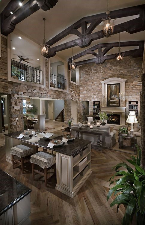 rustic open floor plan stone walls high ceilings with wood beams plus walkway over looking the first floor living roomkitchen