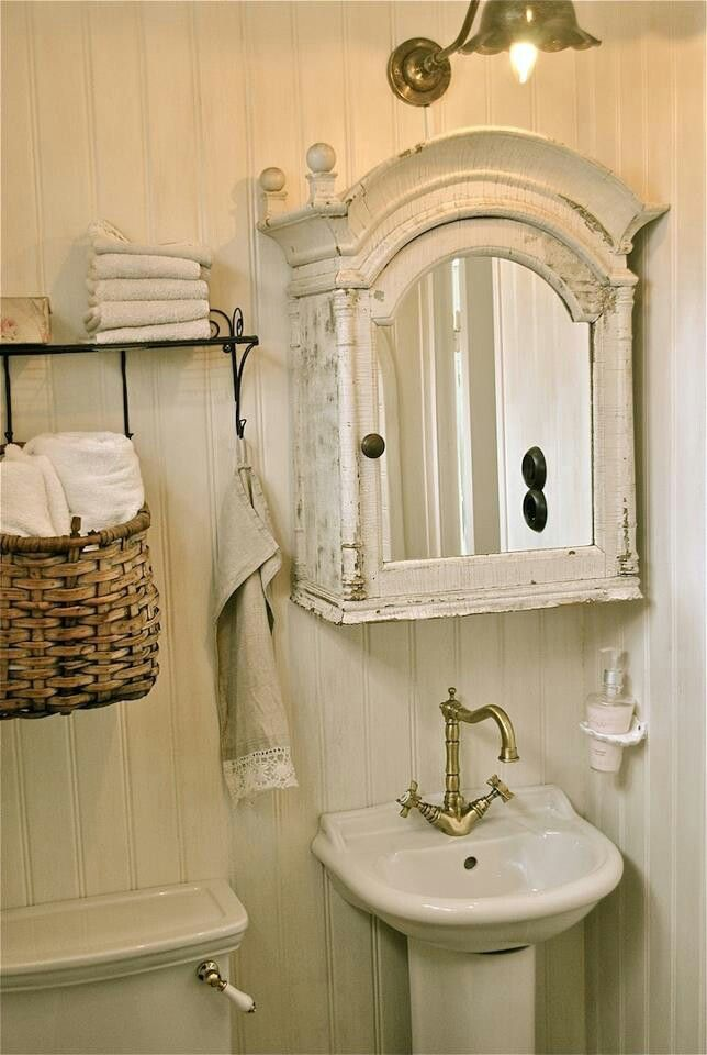 White bathroom with bead board walls. I love the architectural detail on the vintage medicine cabinet and the towels hanging in basket.