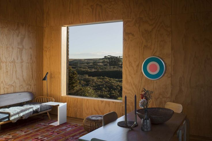 One of the cabins has a plain ply interior. The sofa is by Ercol, the 'AJ' floor lamp is by Arne Jacobsen and the artowkr is by Julian Dashper. Photograph by Darryl Ward.
