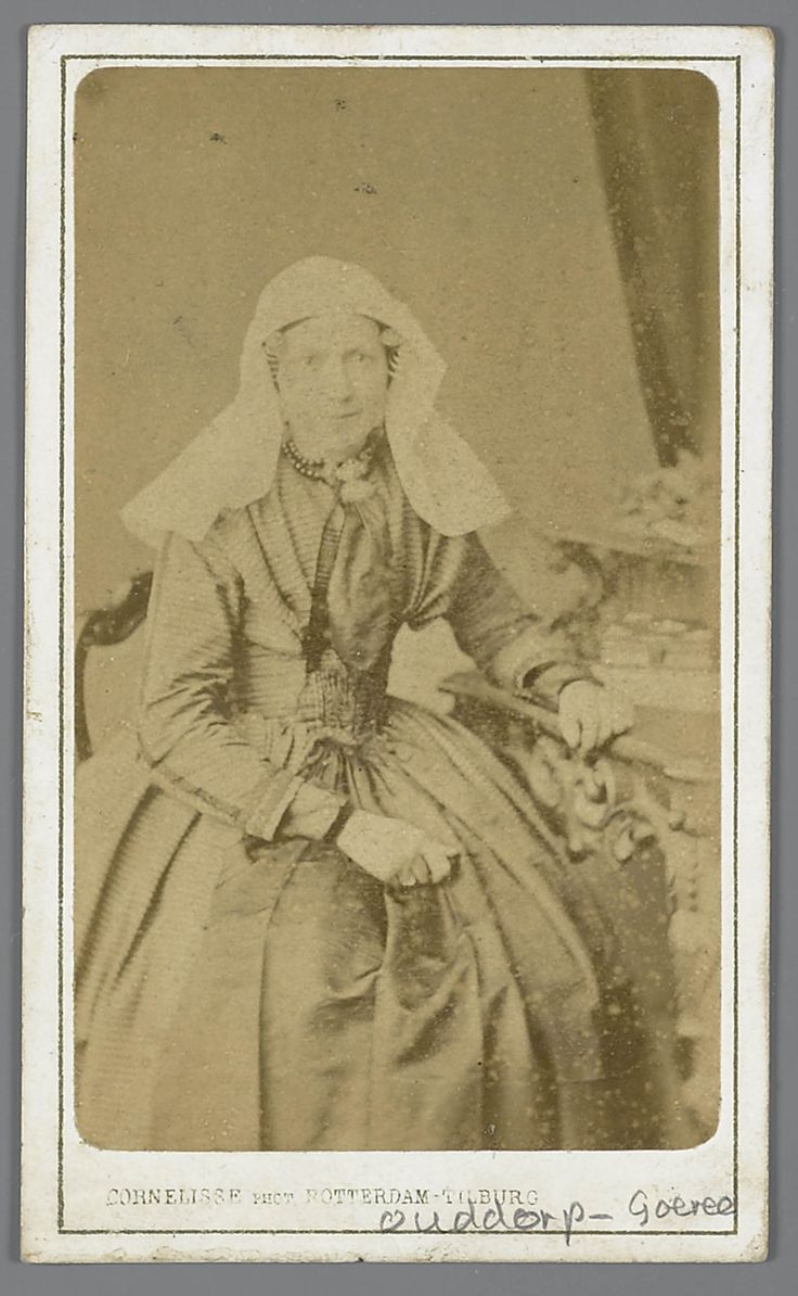Vrouw uit Ouddorp, gekleed in de streekdracht van het eiland Goeree. Onder de sluiermuts draagt de een ondermuts met een oorijzer, met 'krullen' aan de beide uiteinden. Boven de krullen is een paar mutsenspelden in de muts gestoken. #GoereeOverflakkee #ZuidHolland