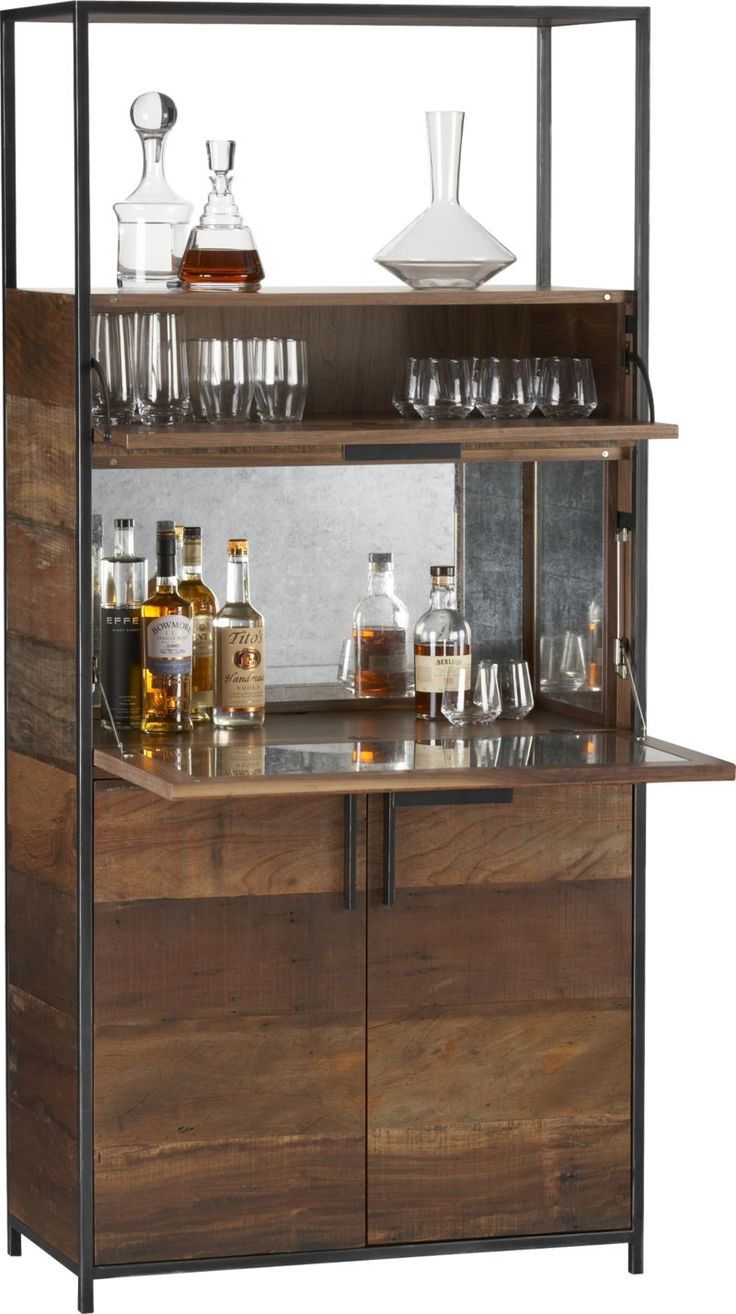 Handsome hideaway for the well-stocked bar frames wide horizontals of warm weathered wood in the strong vertical of its black iron supports.  Centerpiece shelf opens into a generous mirrored bar area lined with silver leaf for a vintage look that adds sparkle to the great colors of wines and spirits.  Glassware is within easy reach in the drop-down shelf above, with an open shelf at the top to showcase carafes, decanters or other decorative accents.