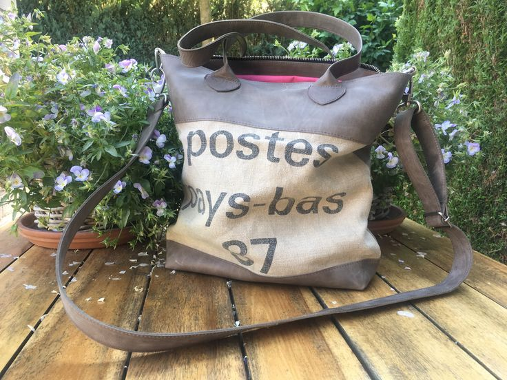 Hand/shoulderbag, made of a 30 test old used dutch postbag and beige leather. Zipperclosed
